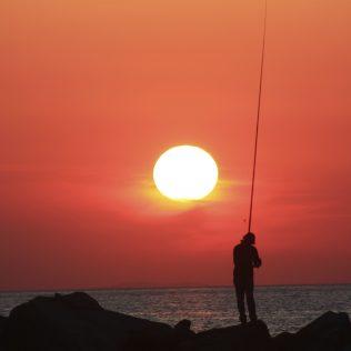 Meer Sonnenuntergang und ein Fischer